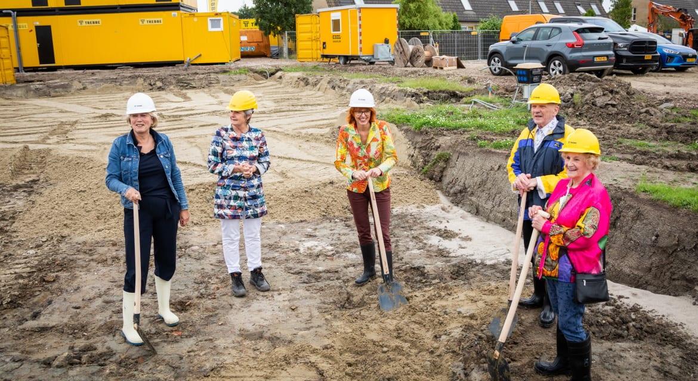 Anita Tijsma (Acantus), Annalies Usmany-Dallinga (wethouder Eemsdelta) en twee huurders hebben voor de start van het bouwproject bij de Fortressestraat in Delfzijl een tijdcapsule gevuld en begraven. Foto: Acantus / Huisman Media